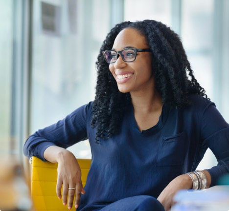 Woman sitting and smiling.