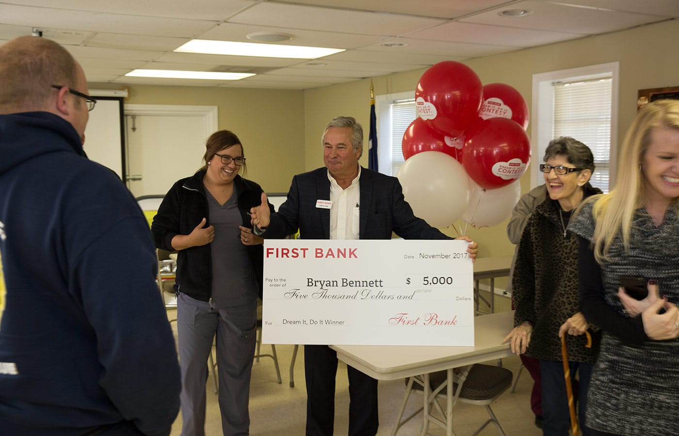 John Long, First Bank regional executive, congratulates Bryan during the surprise.