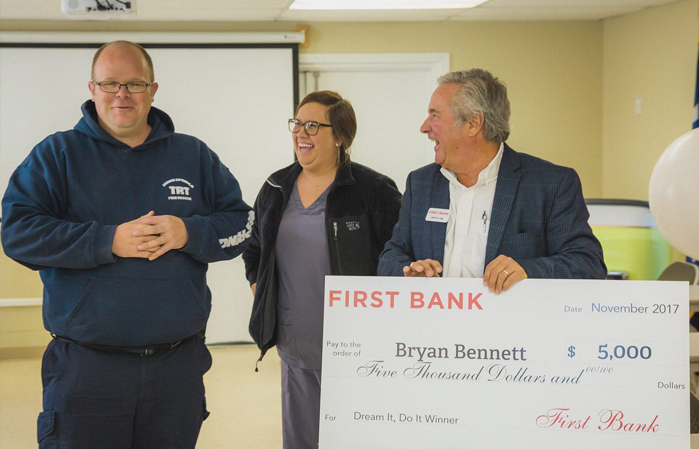 Bryan and Brittany stand side by side with the check.